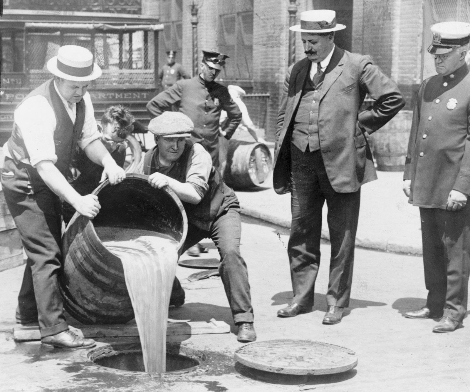 Britannica / New York World-Telegram and the Sun Newspaper Photograph Collection/Library of Congress, Washington, D.C.-New York City őrmester felügyeli, ahogy egy hordó likőrt öntenek a csatornába (c. 1920)