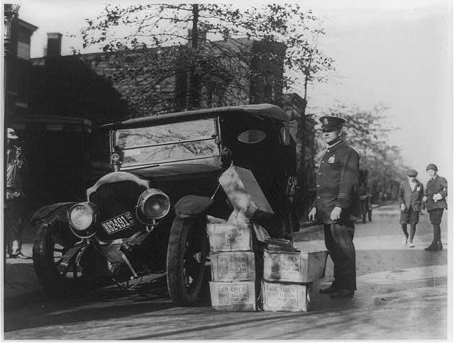 """Wikipedia-Rendőr egy összetört autó mellett, amiben több láda """"Moonshine""""-t, azaz jó minőségű italt találtak (1922)"""