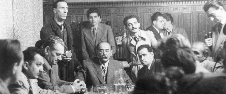 Kossuth Lajos tér, parlamenti szoba 1956. október 23-án. Szemben ül Nagy Imre miniszterelnök, mellette jobbra ül Hidas István, a minisztertanács első elnökhelyettese, őmögötte áll Pongrátz Ernő. A kép jobb szélén könyvekkel a kezében Sinkovits Imre színmű