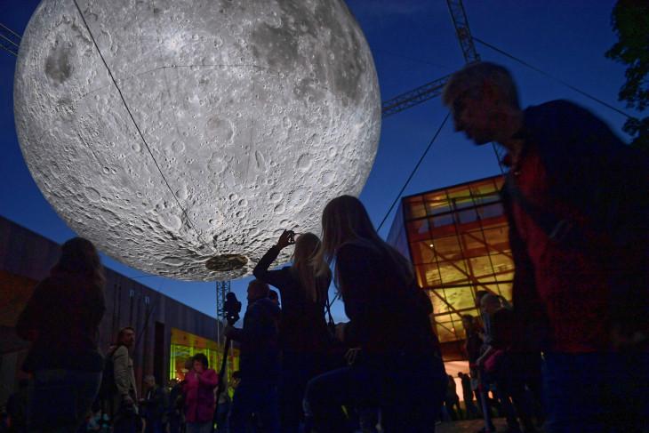 MTI/PAP/Marcin Obara-Luke Jerram brit művész a Hold múzeuma című installációját fényképezi egy látogató a varsói Kopernikusz Tudományos Központnál 2019. május 30